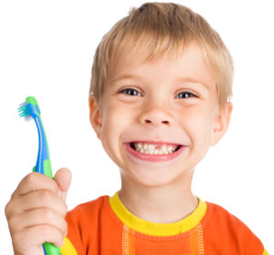 little boy smiling holding toothbrush