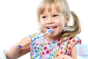 little girl with blond pigtails brushing her teeth
