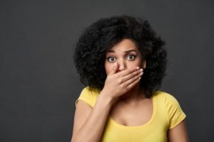 Embarrassed woman covering her mouth after making common teeth whitening mistakes