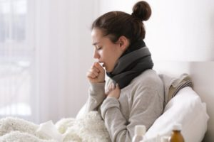 Woman at home coughing from COVID-19