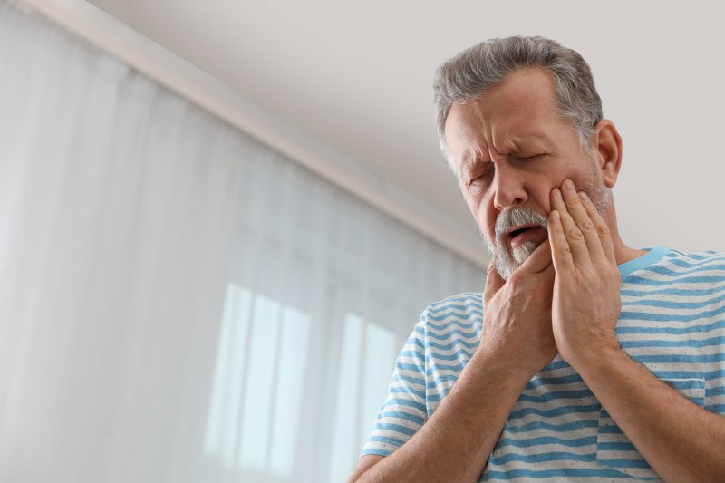 an older gentleman inside his home and holding his cheek in immense pain