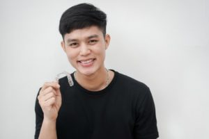 young man in black shirt holding Invisalign aligner