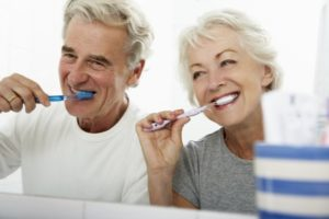 elderly couple following dental hygiene tips by brushing their teeth